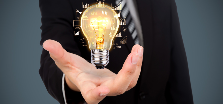 Businessman holding a lit up lightbulb in hand representing innovative thinking