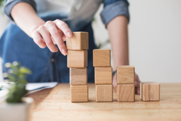 Business professional stacking up blocks