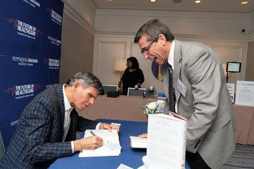 Keynote speaker signing books he authored at the Future of Healthcare Symposium
