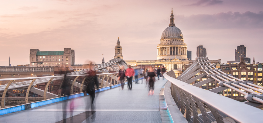 People walking across the millenium bridge near St. Paul's Cathedral in London, United Kingdom