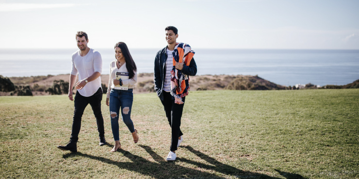 Three students walking on lawn at Pepperdine University